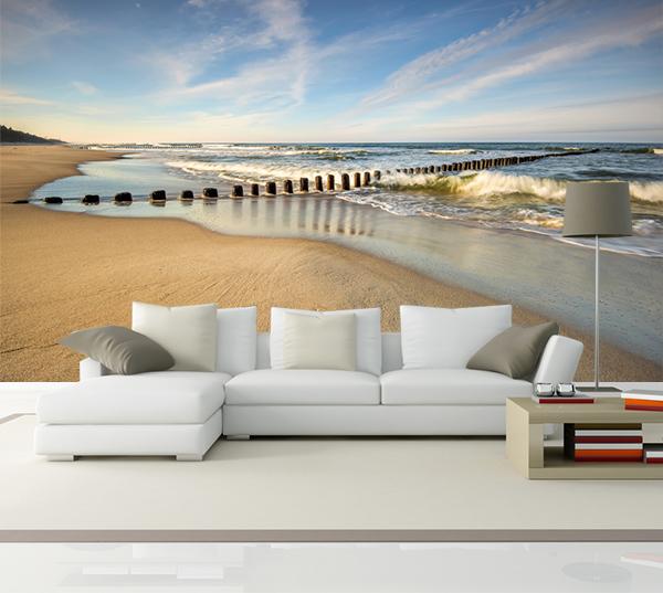 fotobehang van een verlaten strand waar de zee wild het strand ...